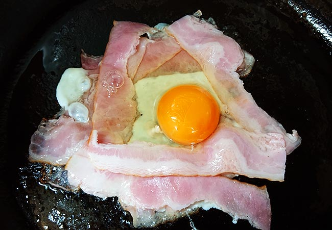 敷き詰めたベーコンの真ん中に卵を落とす