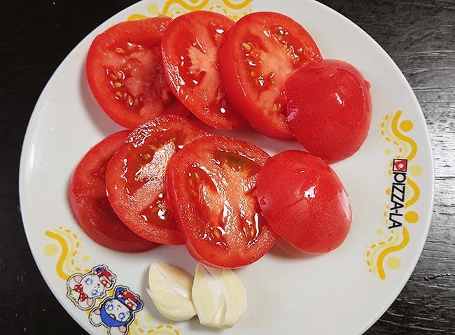 トマトとニンニクをスライスする