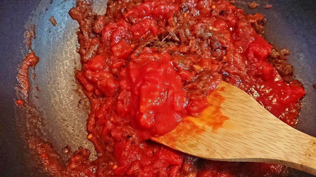 玉ねぎに水分が抜けたら、トマトを加えて炒める。